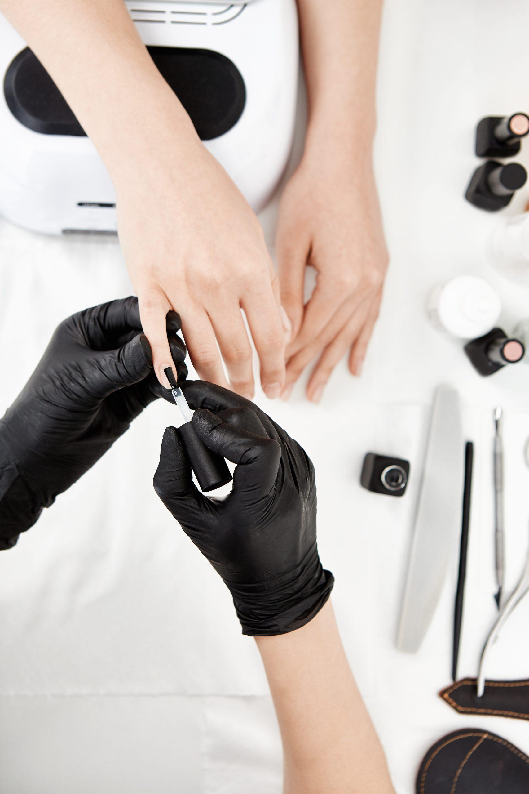 nail artist gloves applying base coat little finger scaled
